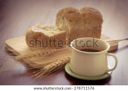 Cup of coffee with toast of bread and dry wheat on the table - stock photo