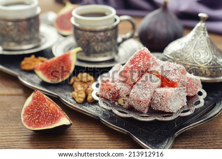 Cup of coffee with turkish delight  and metal oriental tray on wooden background - stock photo