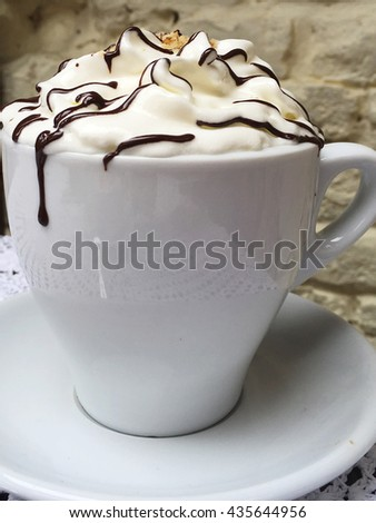 Cup of coffee with whipped cream on white plate. Whipped cream and coffee. Cozy white cup for your text. Shabby coffee. - stock photo