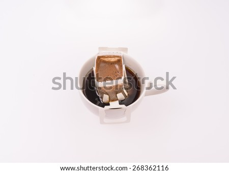 Cup of dripping fresh coffee, blended coffee on paper filter - stock photo