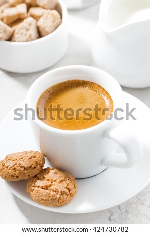 cup of espresso and almond cookies on a white table, vertical