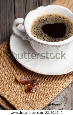 Cup of espresso and brown sugar on old wooden background, selective focus