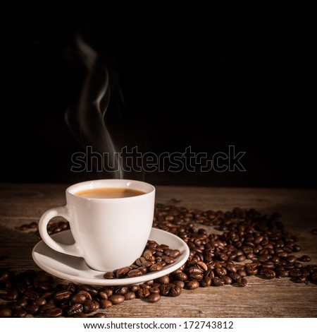 Cup of espresso coffee and coffee beans on wooden background