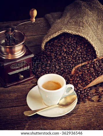 Cup of espresso coffee, coffee beans and old coffee grinder on the wooden table. - stock photo