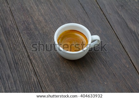 Cup of espresso coffee on wood background vintage tone, shot from above shallow depth of field - stock photo