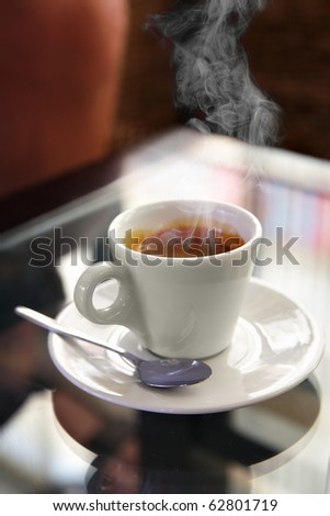 Cup of espresso coffee with steam on the table - stock photo