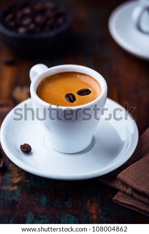 Cup of espresso crema with coffee beans - stock photo