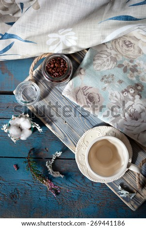 Cup of espresso set on a wooden table with coffee beans, a cup and table linens, natural light setting. - stock photo