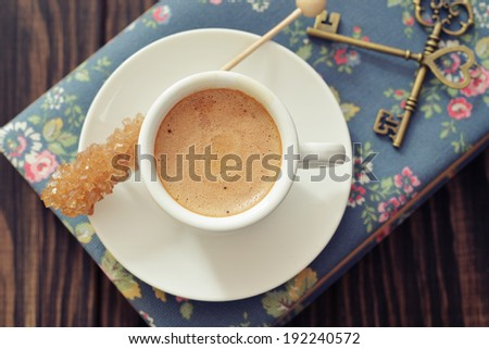 Cup of espresso with candy sugar on wooden background