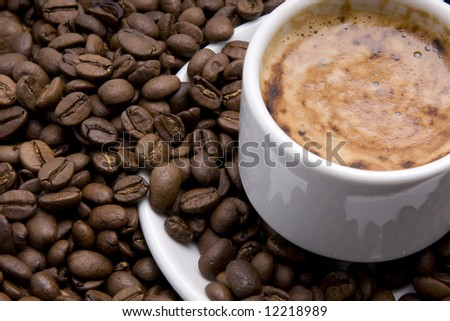 cup of espresso with froth surrounded by coffee beans - stock photo