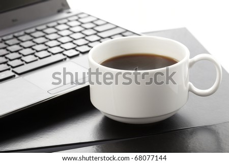 Cup of fragrant coffee on a laptop