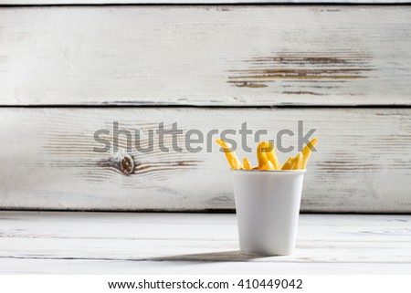 Cup of french fries. White table with fries cup. Crispy and delicious food. High-fat snack in bistro.  - stock photo
