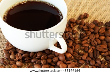Cup of fresh brewed coffee with roasted coffee beans on straw placemat