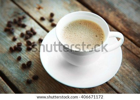 Cup of fresh coffee with beans on wooden background - stock photo