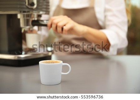 Cup of fresh espresso with female barista on background