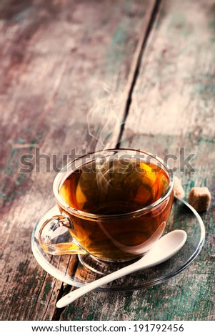 Cup of fresh herbal tea  on vintage wooden background.  Selective focus, vertical. Toned image. - stock photo