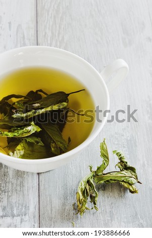 cup of fresh tea from the dried leaves of mint on a table