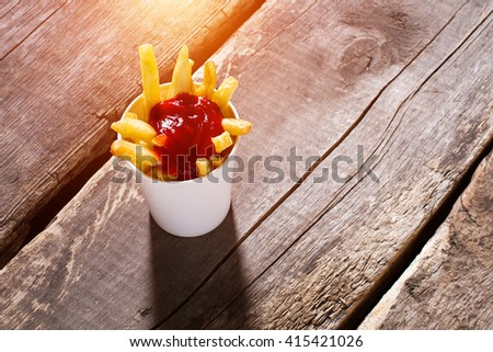 Cup of fries with ketchup. French fries with tomato sauce. Portion of fries on table. Special sauce for snacks. - stock photo