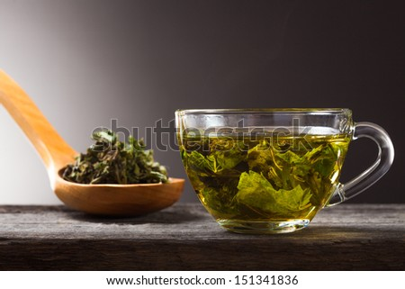 Cup of green mint tea and spoon with dry mint - stock photo