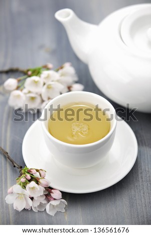 Cup of green tea and japanese cherry blossom on blue background, selective focus