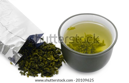 Cup of green tea and pack of green tea leaves, traditional japanese service with healthy fresh tea leaves in the hot water and zen style brown clay cup