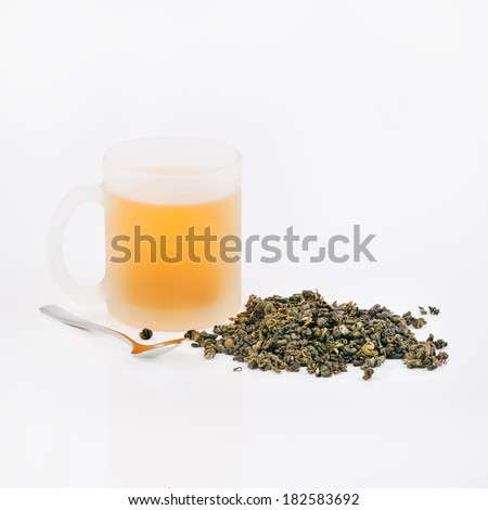 Cup of green tea, green tea leaves and silver spoon on white background