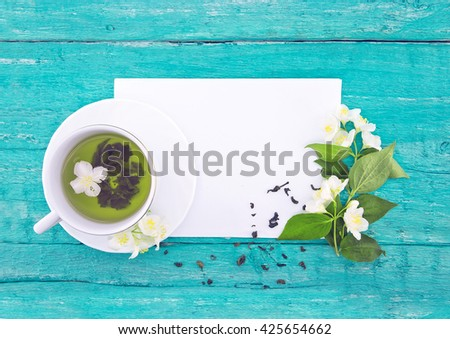 Cup of green tea with jasmine flowers on turquoise rustic wooden background with empty card for greeting message. Mother's Day and spring background concept. Holiday mock up. Top view. - stock photo