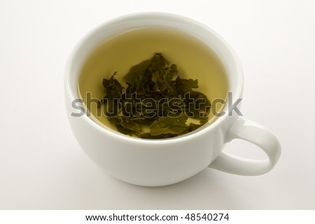 cup of green tea with leaves floating isolated on wite - stock photo