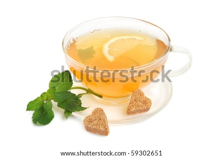 Cup of green tea with mint leaves, lemon and heart-shaped cane sugar on white background - stock photo