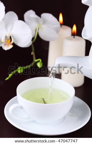 cup of green tea with white orchid- Tea Time - stock photo