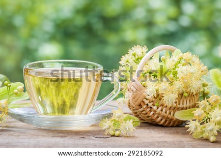 Cup of healthy linden tea and wicker basket with lime flowers, herbal medicine. - stock photo
