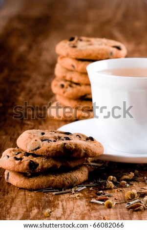 cup of herbal tea and some fresh cookies closeup on wooden table