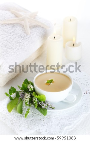 cup of herbal tea on a white background with candles, healthy lifestyle - stock photo
