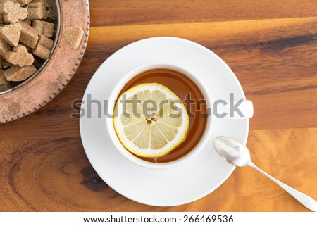 Cup of herbal tea served in a white cup and saucer with a slice of lemon and brown sugar cubes in a sugar bowl on a wooden table viewed from above - stock photo