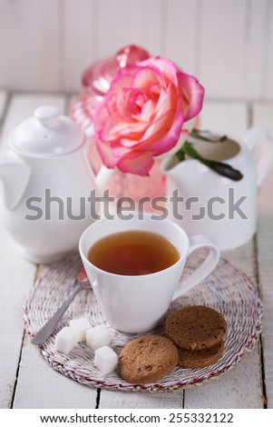 Cup of herbal tea served wit pastry and sugar on white wooden background.  Selective focus. - stock photo