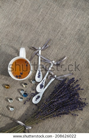 cup of herbal tea with a porcelain spoon and a lavender bouquet on linen fabric  - stock photo