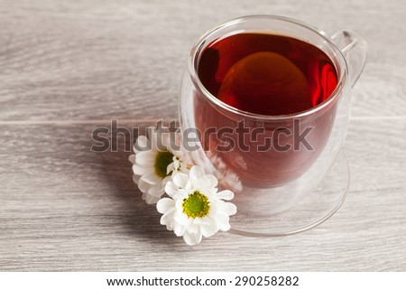cup of herbal tea with chamomile flowers on wooden background - stock photo