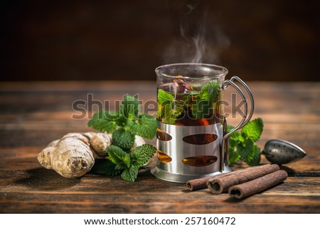 Cup of herbal tea with fresh mint on wooden table - stock photo
