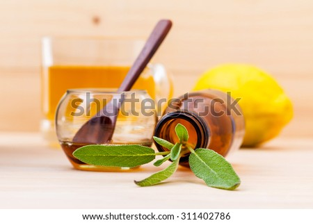 Cup of herbal tea with  fresh sage ,honey and lemon on wooden background. - stock photo