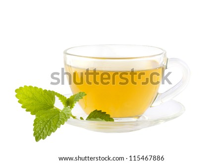 Cup of herbal tea with green mint leaves on the saucer. Isolated on white with clipping path. - stock photo