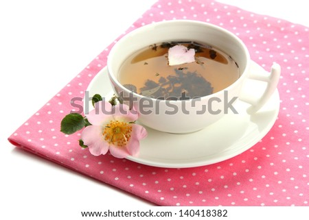 Cup of herbal tea with hip rose flowers, isolated on white