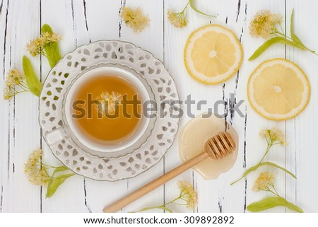 Cup of herbal tea with linden flowers, lemon and honey on a old wooden background. Top view - stock photo