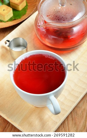 Cup of hibiscus tea and cookies - stock photo