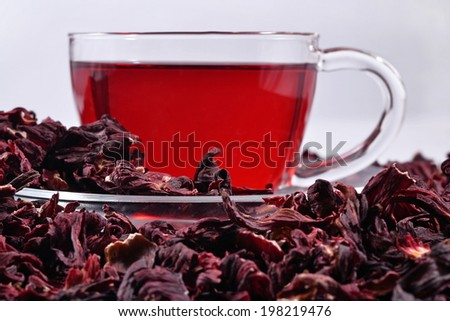 Cup of hibiscus tea in a heap of dried petals of hibiscus  - stock photo