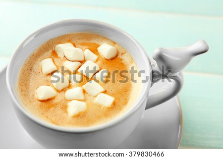Cup of hot cacao with marshmallow on blue table
