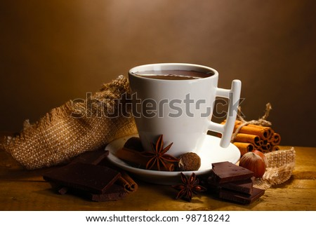 cup of hot chocolate, cinnamon sticks, nuts and chocolate on wooden table on brown background