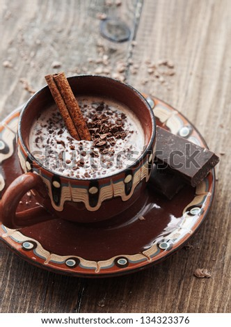 Cup of hot chocolate cocoa with cinnamon sticks on vintage wooden background, selective focus - stock photo