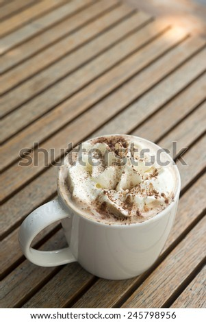 Cup of hot Chocolate topping with whipping cream and cocoa powder on wooden table