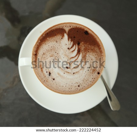 cup of hot chocolate with art creamy milk in cafe - stock photo
