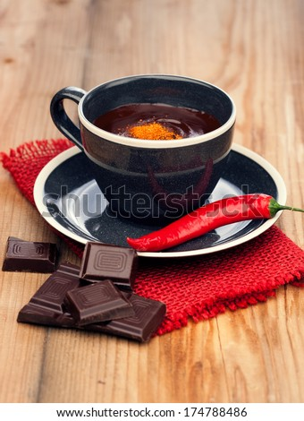 Cup of hot chocolate with chili pepper on old wooden table  - stock photo